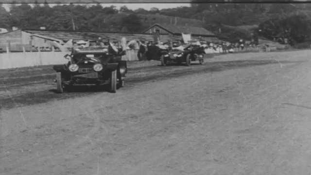 1910s: Decorated cars full of people pull onto road for parade.