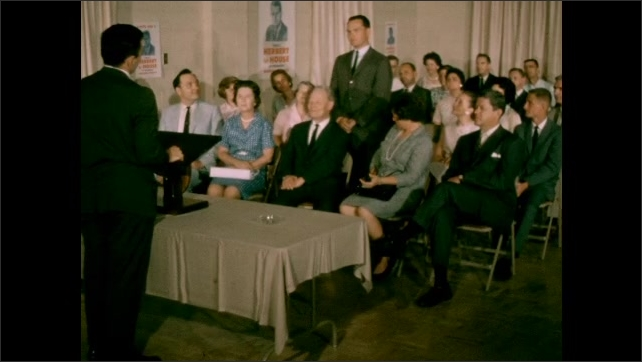 1950s: Man speaks to room full of people sitting in folding chairs. Man raises hand, stands up talking then sits down. Man continues talking to room.
