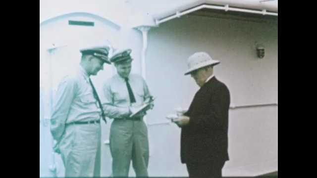 1950s: Men speak on deck of ship.  Water.  City.  Mountains.  House.