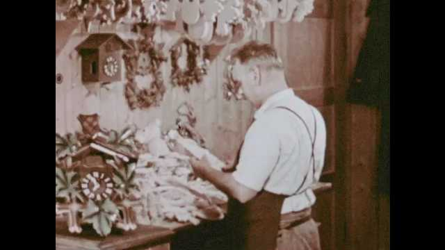 1950s: Man at table building clocks. People on field load bundles of hay onto cart.