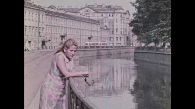 1970s Soviet Union: Woman looks over railing at water. Statue of Nicholas I. People point at Winter Palace. Woman takes photos at Peterhof Palace. Fountains at admiralty building. Warship in water.