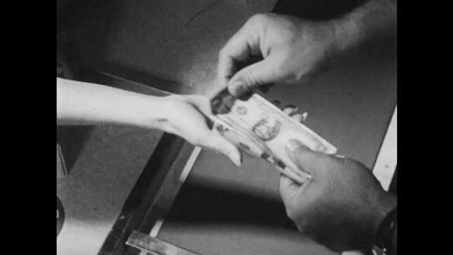 1950s: Grocery store.  Cashier hands change to woman.  Woman puts money in purse.  Little boy stands.  Men look at fishing net.