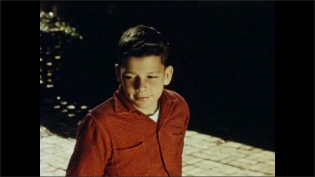 1950s: Boy sitting outside, looks up. Smoke rising from chimney. Boy turns. Close up, fire burning in pit.