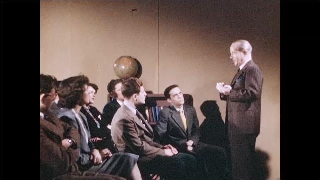 1950s: Boy frowns. Man speaks and gestures. People applaud. Man sits.
