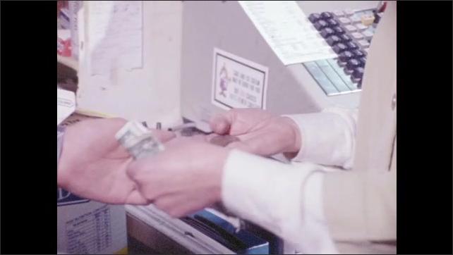 1970s: Cash register amount. Close-up of keys on cash register. Woman counts change for customer.