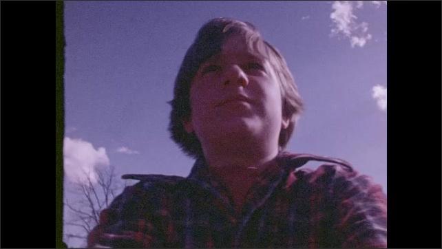 1970s: Boy rides bike.