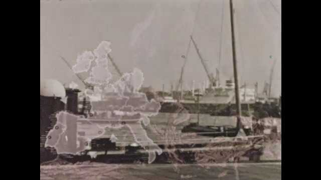 1950s: tug boats in river as larger boats are docked behind them
