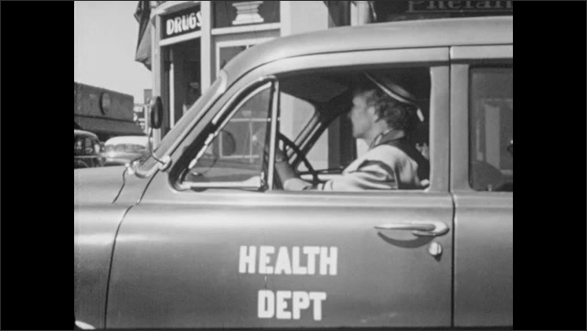 """1950s: Father holds onto bike as son rides across street.  Woman drives car labeled """"HEALTH DEPT.""""  Police officer directs traffic."""