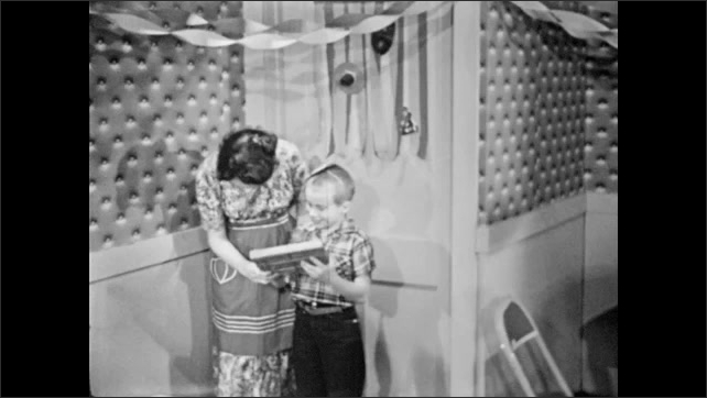 1950s: Woman answers door.  Mailman delivers package.  Little boy opens package.  Woman holds paper.
