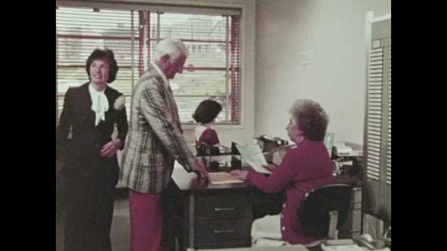 1970s: People in office, man and woman walk to map on wall. Pan across street to men working. Woman at desk. Woman presenting to people at table. Man stands from table, people raise hands.