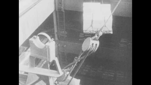 1940s: Crane loads pallet of boxes onto boat. Man exits plane. Man speaks at press conference. Bombs fall on ships in Pearl Harbor.