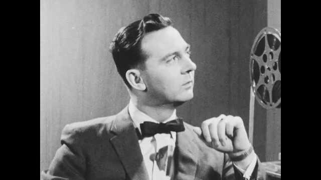 1940s: Man sits next to projector, talks. Man stands next to map on chalkboard, talks. Man sits down at desk. Man stacks film reels.