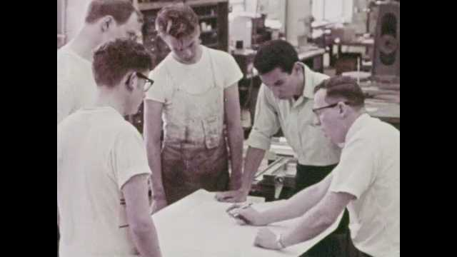 1960s: Men, boys around table. Man and boy talking in office, shake hands. Pan of girl walking, girl enters building. Girl talking to woman at desk.