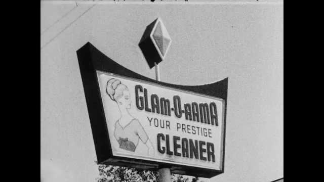 1960s: Dry cleaners sign. Man sits behind desk, talks. Woman sits across from man, takes notes.