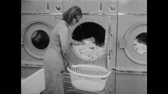 1960s: Woman removes clothes from dryer, puts clothes in basket. Row of washing machines. Dry cleaning machines. Woman folds laundry. Man speaks into microphone.