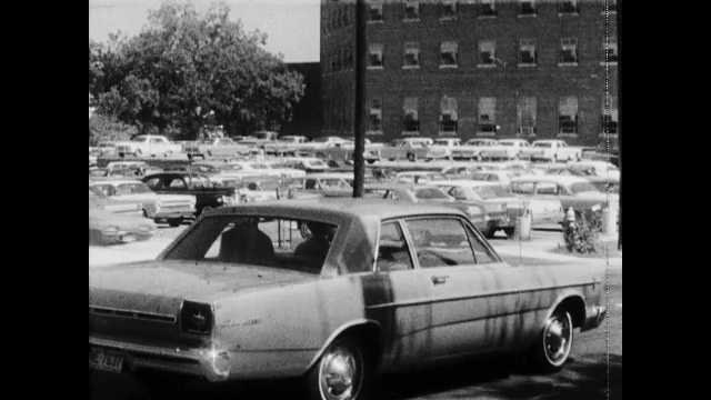 1960s: Cars turn down street. Parking lot. Sign spins around. Building.