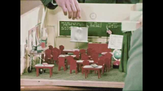 1960s: Man moves models in diorama of classroom and talks to colleagues. Men and woman sit at table with diorama and talk. Hands move models in diorama of classroom.