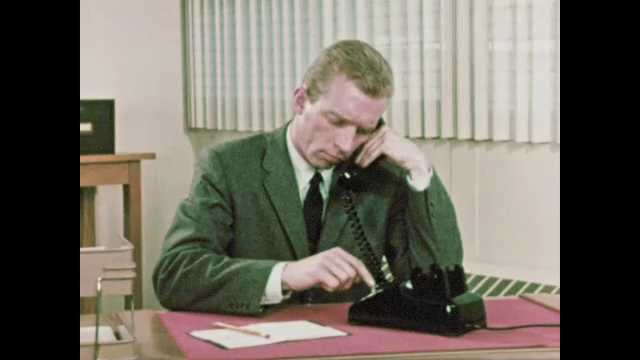 1960s: Man dials rotary phone at office desk. Woman enters AV office and speaks to man, Woman sits at office desk while man speaks and opens file cabinet.