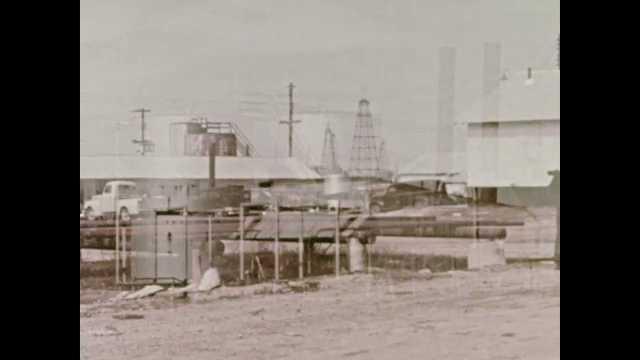 1960s: Men carry pipe.  Men assemble oil well.