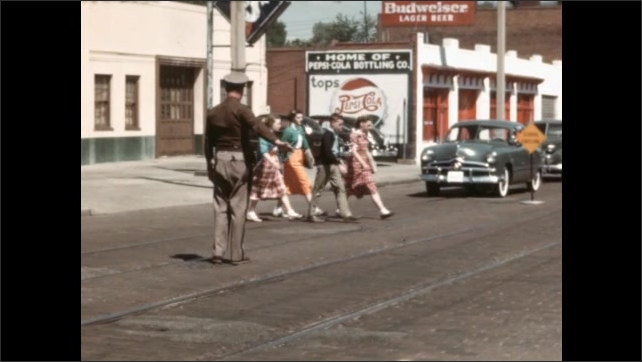 1950s: Police officer stands in intersection, blows whistle, holds out hands. Officer motions for children to cross the street, children cross. Officer motions for cars to go, cars drive.