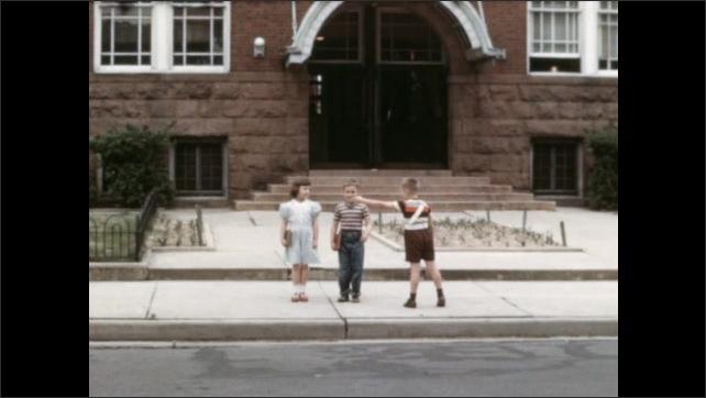 1950s: Boy stands on sidewalk, looks around. Children walk up to boy, turn and walk down sidewalk. Officer guides children across street.