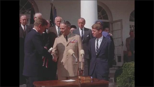 1960s Washington DC: White House lawn.  John F. Kennedy speaks.  People clap.  General speaks.  Robert F. Kennedy stands.