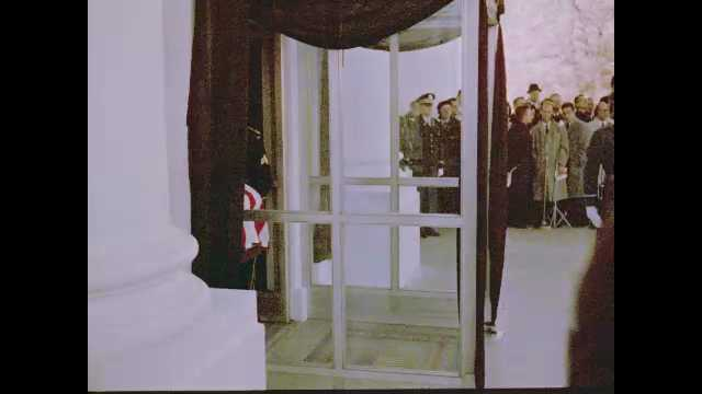 1960s Washington DC: Spectators watch as soldiers carry flag-draped casket out of White House.