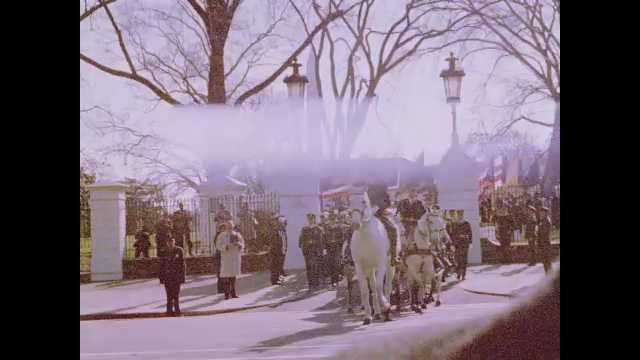 1960s Washington DC: Funeral procession leaves White House driveway. Soldiers on horseback and foot march near flag-draped casket. Cars follow funeral procession.