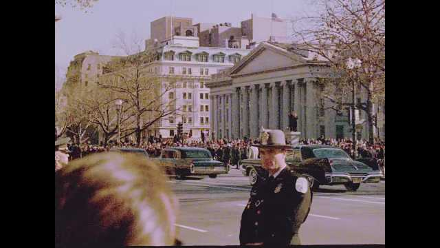 1960s Washington DC: Spectators and police officers watch funeral cars drive down road in Washington DC.