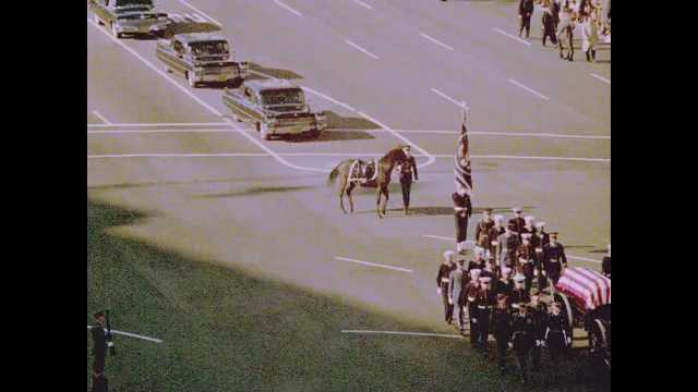 1960s Washington DC: Soldiers march before Kennedy funeral procession on streets of Washington DC. Cars follow soldiers and funeral wagon on street.