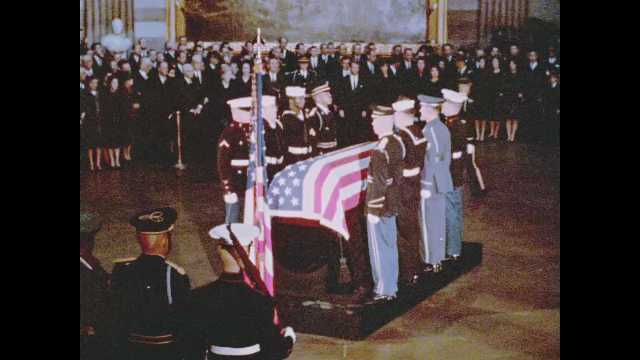 1960s Washington DC: solders step down from platform with flag-draped coffin as crowd watches