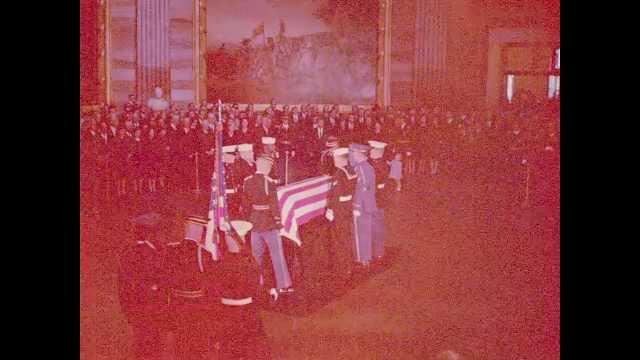 1960s Washington DC: man reads speech as crowd listens near soldier and flag-draped coffin, Caroline Kennedy fidgets