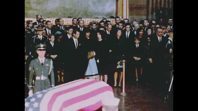 1960s Washington DC: Jackie, Bobby and Caroline Kennedy in crowd near soldier and flag-draped coffin as President Lyndon Johnson and a soldier bring wreath on stand near coffin