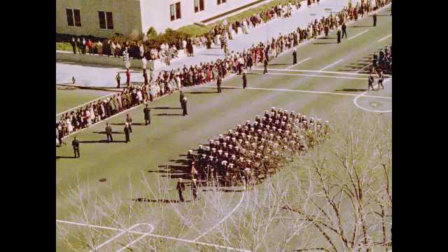 1960s: Funeral procession of soldiers in formation march down street for John F. Kennedy's funeral.