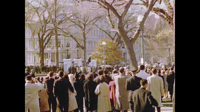 1960s: Crowds of people watch funeral procession for John F. Kennedy. Driving down road by crowds of spectators.