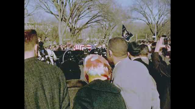 1960s: Crowd of people watch horses pull carriage carrying casket of John F. Kennedy down road. Crowd of people watch, take photographs.