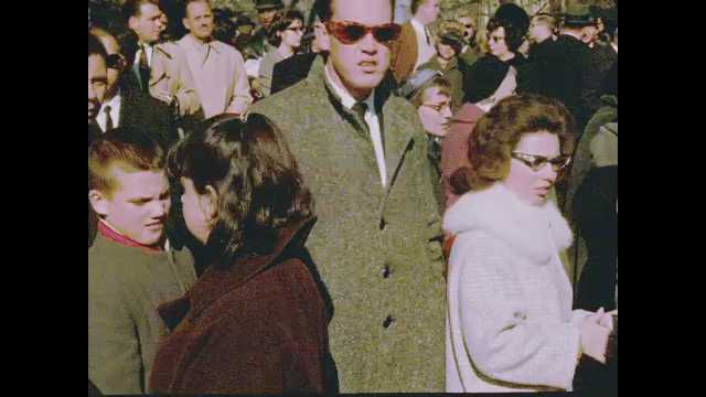 1960s: People in crowd watch funeral procession for John F. Kennedy.