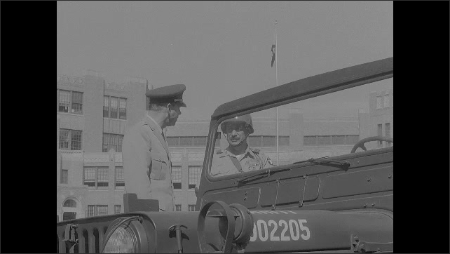 1950s: Man in officers uniform talks to soldier. Man gets into jeep. Men in uniform drive away in jeep.