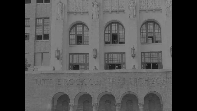 1950s: Film slate. Reflecting pond in front of Little Rock Central High School. Army soldiers stand at entrance to high school. Students crowd together in windows of high school.