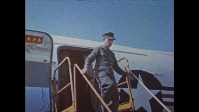 1960s: Helicopter takes off. Staircase rolls up to plane. Newsman films McNamara descending from plane. Switchboard. Clock. General addresses troops and examines arms. Blueprints unrolled. F-11 jet.