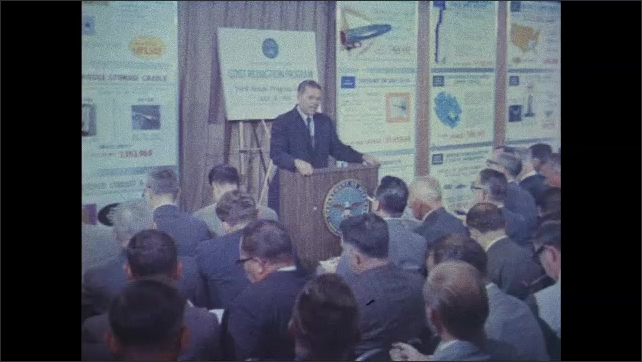 1960s: Soldiers in uniform run together and drop on their stomachs on a battlefield. Helicopters fly over the battlefield. Robert McNamara addresses Press Corp about Dept. of Defense 1965 spending.
