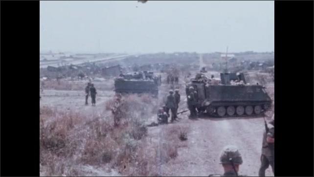 1960s Vietnam: Battlefield.  Dead soldiers.  Men move around field.  Tanks.