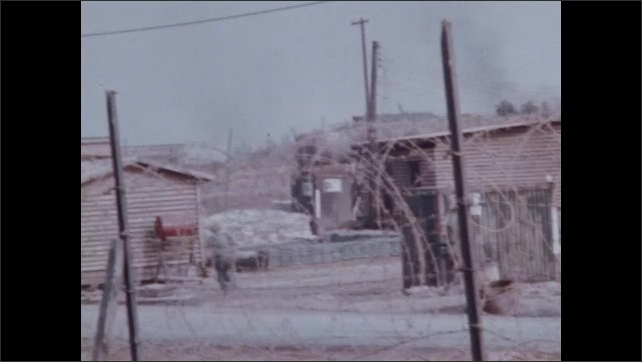 1960s Vietnam: Helicopter.  Power lines.  Military camp behind barbed wire.  Soldiers.