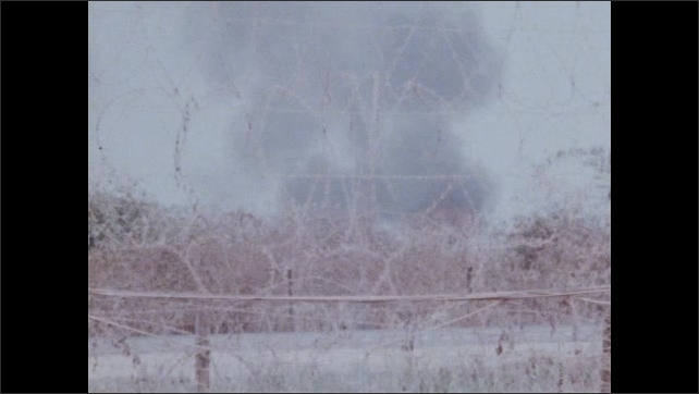 1960s Vietnam: Barbed wire fence.  Tank approaches burning building.