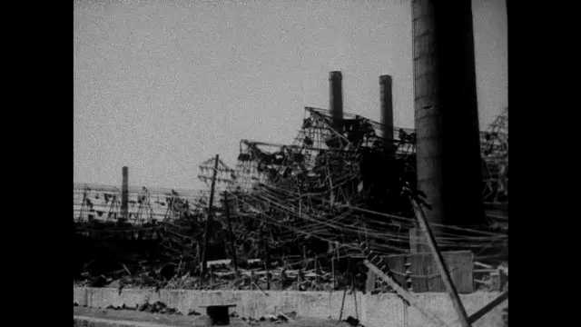 NAGASAKI, JAPAN 1940s: Bombed out walls and smokestacks of destroyed factory sit near hills.  Flames dance on wreckage near metal girders. Interior of bombed out factory buildings.
