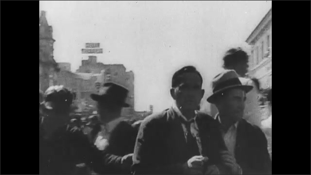 1920s: People in street in protest. Man escorted by police down street. Gas rises from street filled with protestors. Police collide with protestors in street. Injured man. Police and protestors.