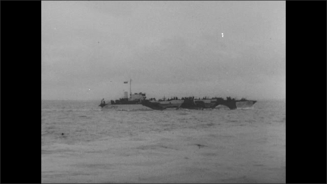 1940s: Fleet of boats carrying soldiers. Boats carry soldiers. Boat goes by sinking boat.