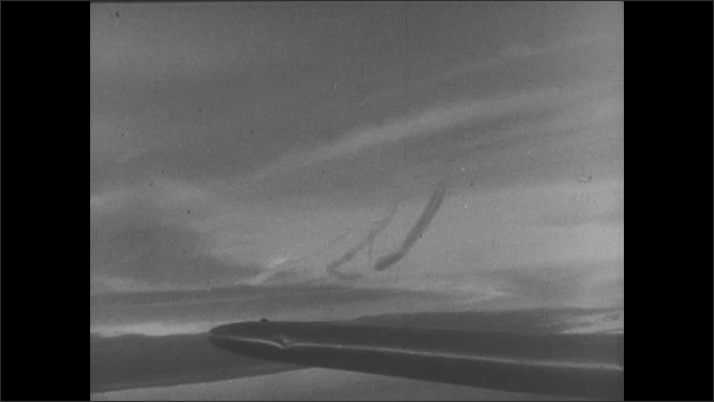 1940s: Moon of tip of airplane wing in sky. Bombs explode on ground below. Bomber in sky. Bombs explode on ground below. Bomber at night. Bombs on ground.