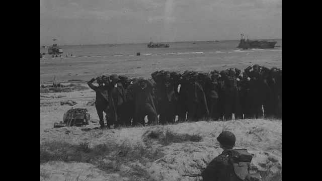 France 1940s: Pan of captured soldiers on beach with allied soldiers. Medics tending to wounded man. Medic giving man injection. Medics with wounded men on beach.