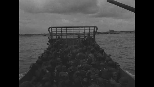France 1940s: Tracking shot from landing craft, soldiers moving toward beach. Landing craft stopping at beach. Soldiers exiting craft.
